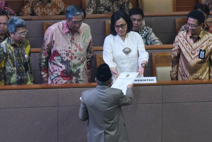 Menteri Keuangan Sri Mulyani (kedua kanan) didampingi Wakil Menteri Keuangan Mardiasmo (kedua kiri) menerima pandangan fraksi atas pertanggungjawaban pelaksanaan APBN 2017 dari anggota DPR fraksi PKS Refrizal (tengah) saat Rapat Paripurna di Kompleks Parlemen Senayan, Jakarta, Selasa (10/7).