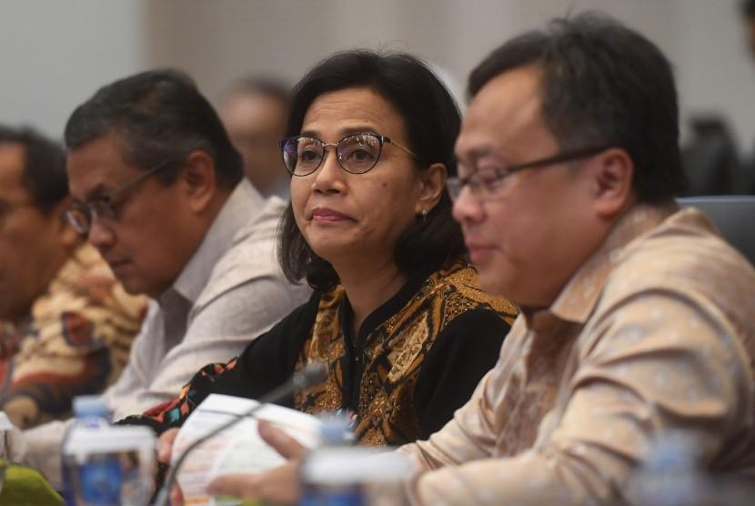 Menteri Keuangan Sri Mulyani (tengah) bersama Gubernur BI Perry Warjiyo (kiri) dan Menteri PPN/Kepala Bappenas Bambang Brodjonegoro (kanan) mengikuti rapat kerja dengan banggar DPR di Kompleks Parlemen, Senayan, Jakarta, Senin (15/10)