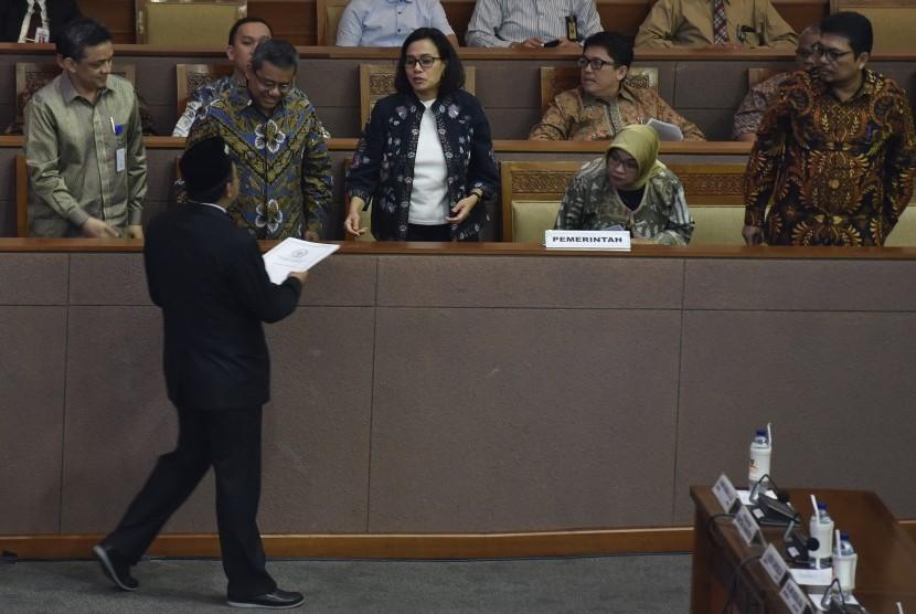 Menteri Keuangan Sri Mulyani (tengah) menerima laporan hasil pembahasan RAPBN 2019 dari Wakil Ketua Banggar DPR Jazilul Fawaid saat Rapat Paripurna ke-30 di Kompleks Parlemen Senayan, Jakarta, Kamis (12/7).