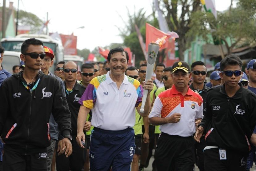 Menteri Koordinator Bidang Kemaritiman, Luhut Binsar Panjaitan membawa obor Asian Games 2018 di NTB, Kamis (26/7).