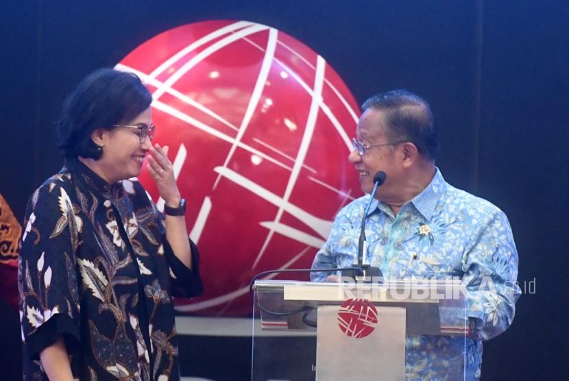 Menteri Koordinator Bidang Perekonomian Darmin Nasution (kanan) berbincang dengan Menteri Keuangan Sri Mulyani (kiri) saat pembukan perdagangan 2019 di Bursa Efek Indonesia, Jakarta, Rabu (2/1/2019).