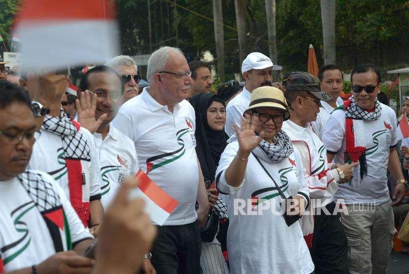 Menteri Luar Negeri (Menlu) RI Retno Marsudi (kedua kanan) dan Menlu Palestina Riyad al-Maliki (tengah)jalan santai bersama dalam acara Walk for Peace and Humanity di kawasan car free day (CFD) Jakarta, Ahad (14/10).