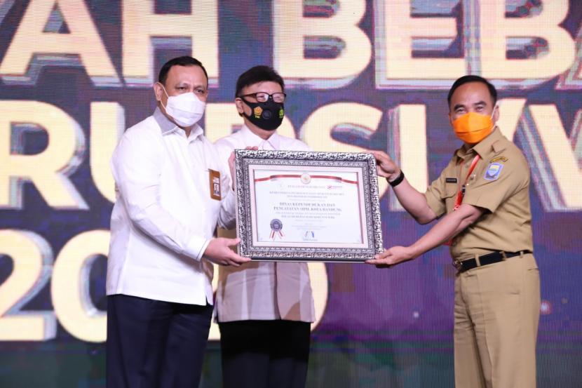 Menteri PANRB Tjahjo Kumolo (tengah) didampingi Ketua KPK Firli Bahuri (kiri) menyerahkan penghargaan kepada Kepala Disdukcapil Kota Bandung Tatang Muchtar (kanan) di Hotel Fairmont, Jakarta (21/12).