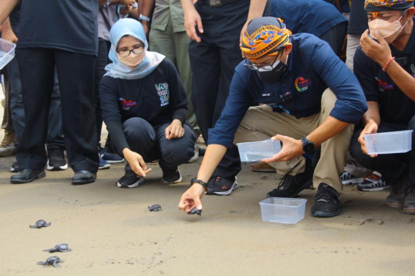 Menteri Pariwisata dan Ekonomi Kreatif/Kepala Badan Pariwisata dan Ekonomi Kreatif Sandiaga Salahuddin Uno (kanan) melepas tukik atau anak penyu di kawasan Desa Wisata Pantai Serang, di Blitar, Jawa Timur, Sabtu (16/10/2021).