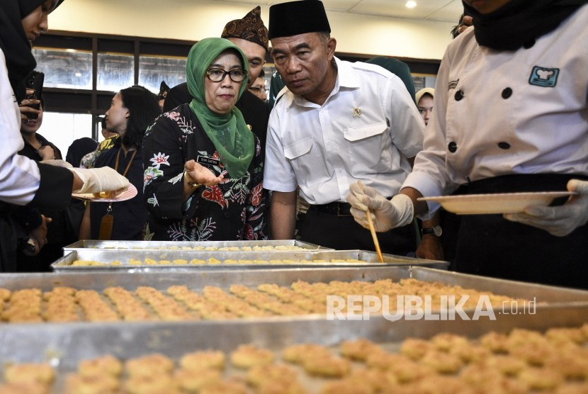 Menteri Pendidikan dan Kebudayaan Muhadjir Effendy (kanan) didampingi Kepala Dinas Pendidikan Provinsi Jawa Barat (kiri) melihat proses pembuatan kue yang dibuat oleh siswa SMKN 9 Bandung saat kunjungan kerja di Kota Bandung, Kamis (21/2).