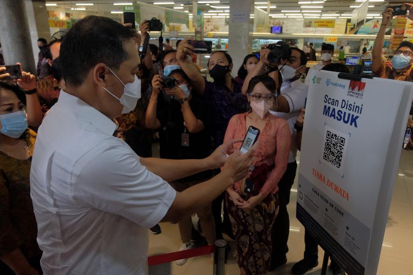 Menteri Perdagangan Muhammad Lutfi (kiri) melakukan pemindaian kode batang sertifikat vaksin COVID-19 melalui aplikasi PeduliLindungi saat kunjungan kerja di swalayan Tiara Dewata, Denpasar, Bali, Sabtu (25/9/2021). Kunjungan Menteri Perdagangan di swalayan tersebut meninjau kesiapan untuk pembukaan dan penerapan SOP PeduliLindungi pada supermarket dan departement store di luar mal sebagai upaya pencegahan penyebaran COVID-19.