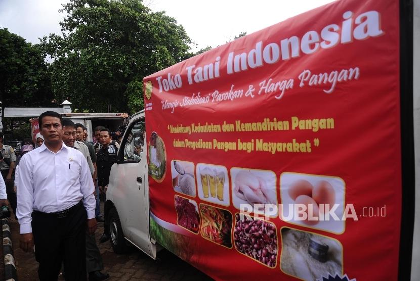 Menteri Pertanian Amran Sulaiman berjalan disamping kendaraan yang akan mendistribusikan bahan pokok untuk Toko Tani Indonesia (TTI) di Jakarta, Senin (6\2).