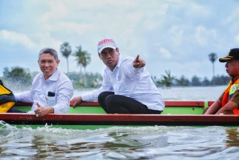 Menteri Pertanian Andi Amran Sulaiman saat meninjau lahan pertanian yang terkena banjir di Kabupaten Wajo, Sulawesi Selatan, Senin (9/7).