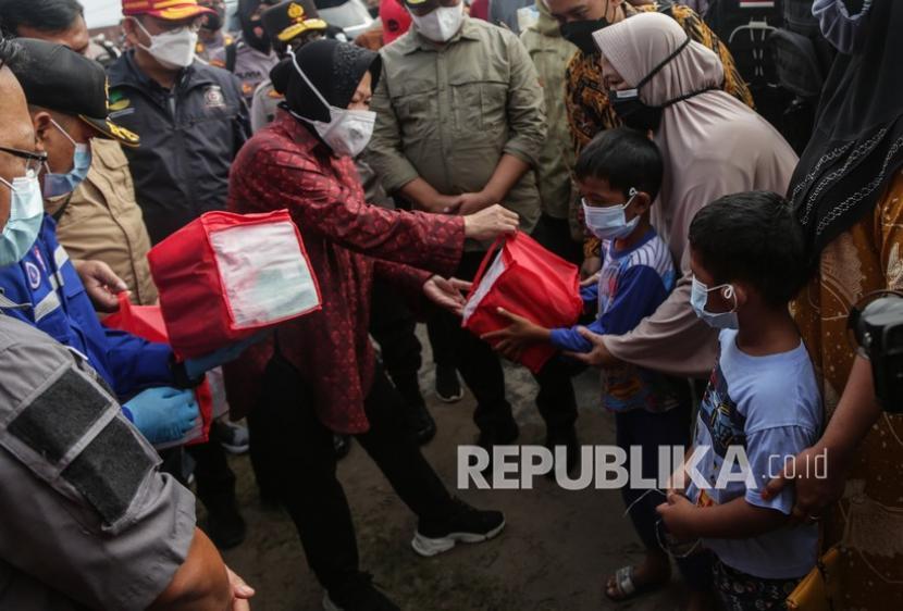Menteri Sosial Tri Rismaharini (kiri) menyerahkan bantuan sosial kepada warga saat kunjungan kerja di dapur umum korban banjir di Jalan Anoi, Palangkaraya, Kalimantan Tengah, Kamis(15/9).