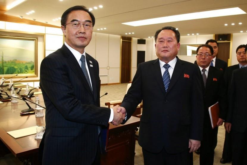Menteri Unifikasi Korea Selatan Cho Myoung-gyon (kiri) berjabat tangan dengan Kepala Delegasi Korea Utara Ri Son Gwon usai pertemuan di Desa Panmunjom di Zona Demiliterisasi di Paju, Korsel, Selasa (9/1).