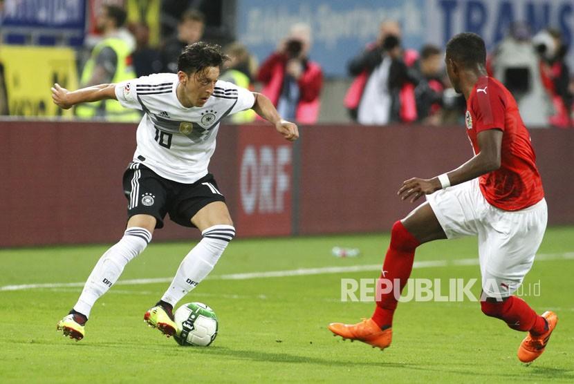 Mesut Oezil  menggocek  bola dibayangin pemain Austria David Alaba dalam pertandingan sepak bola persahabatan antara Austria dan Jerman di Klagenfurt, Austria Sabtu (2/6).