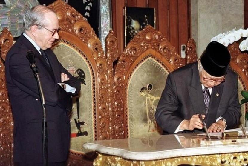 Michel Camdessus, managing director IMF (kiri), dan Presiden Indonesia Soeharto (kanan).