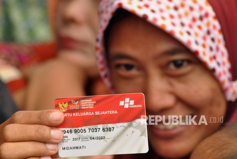 Midahwati, salah satu penerima manfaat Program Keluarga Harapan menunjukkan Kartu Keluarga Sejahtera yang baru diterimanya, di SMKN 1 Kajen, Kabupaten Pekalongan, Senin (15/1).
