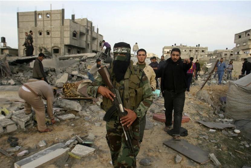 Milisi Hamas berjalan di reruntuhan rumah yang hancur terkena serangan Israel di Rafah, Jalur Gaza, Jumat (16/11).
