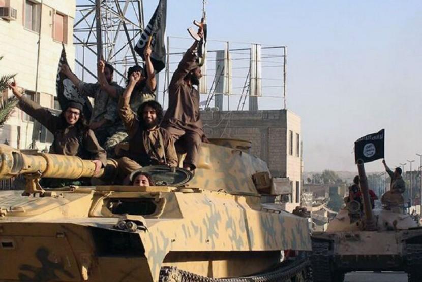 Militan ISIS berparade di atas tank di Suriah.