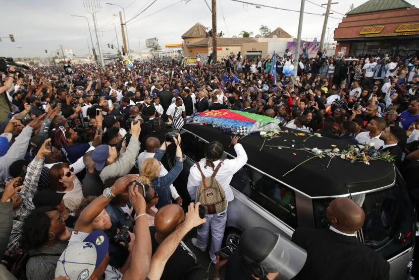 Mobil jenazah membawa mendiang rapper Nipsey Hussle yang dibungkus bendera asal ayahnya, Eritrea di Afrika Timur, melewati jalanan, Kamis (11/4) waktu Los Angeles.