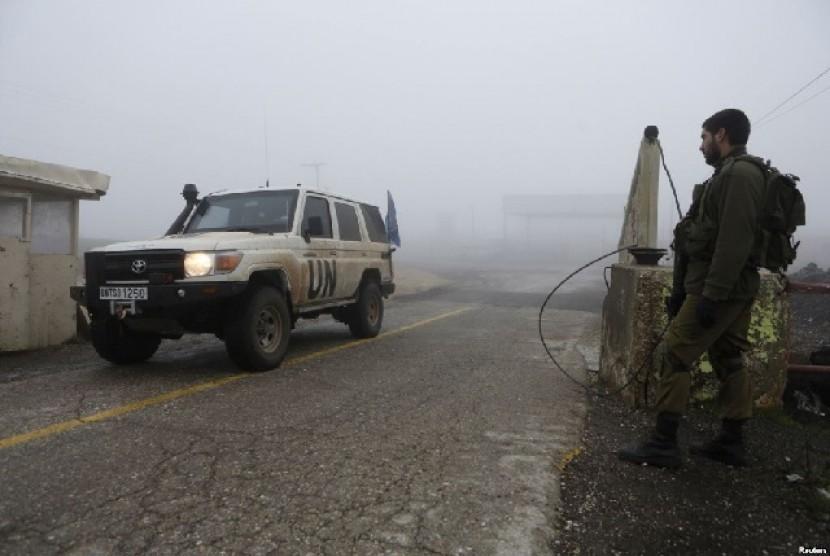 Mobil pasukan perdamaian PBB melewati penyeberangan Quneitra, sementara tentara Israel mengawasi di Dataran Tinggi Golan