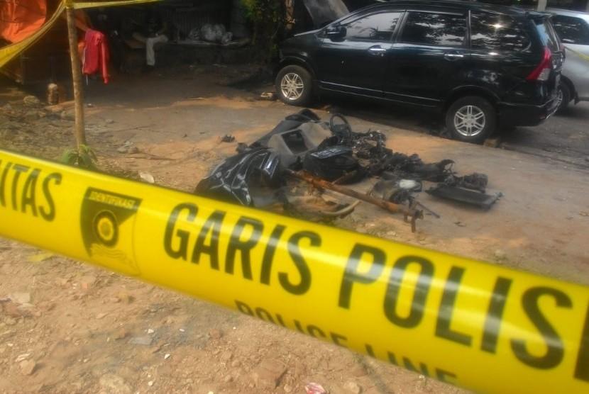 Mobil Xenia warna hitam Nopol B 1247 EKC terongok dan dipasang garis polisi di bengkel mobil di Jalan M Yasin, Kelapa Dua, Cimanggis, Depok. Mobil tersebut merupakan mobil milik Neno Warisman yang terbakar.
