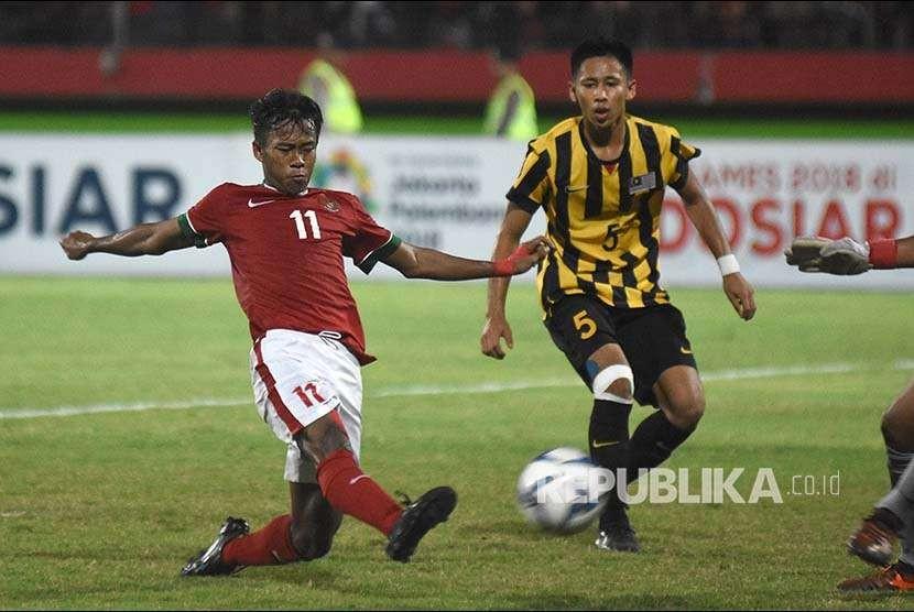 Mochammad Supriadi (kiri) berusaha melepaskan tendangan melewati hadangan pesepak bola Malaysia U-16 Mohamad IkhwanMohd Hafizd (kanan) pada laga semifinal Piala AFF U-16