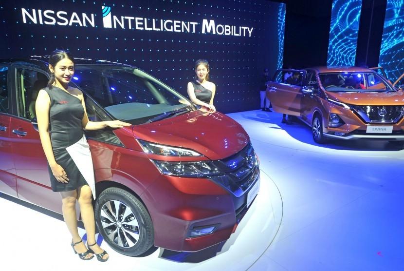 Model berpose di dekat produk terbaru All New Nissan Livina dan All New Nissan Serena saat peluncurannya, di Jakarta, Selasa (19/2).