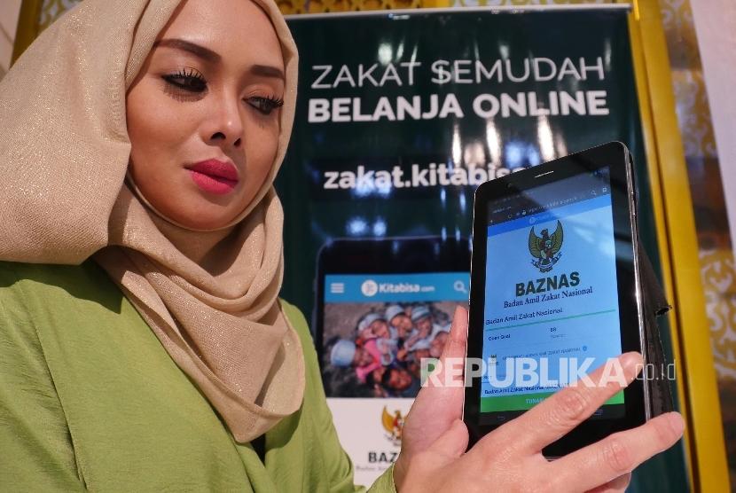 Model memperlihatkan web Zakat Digital pada peluncurannya di Jakarta, Jumat (24/6). (Republika/Darmawan)