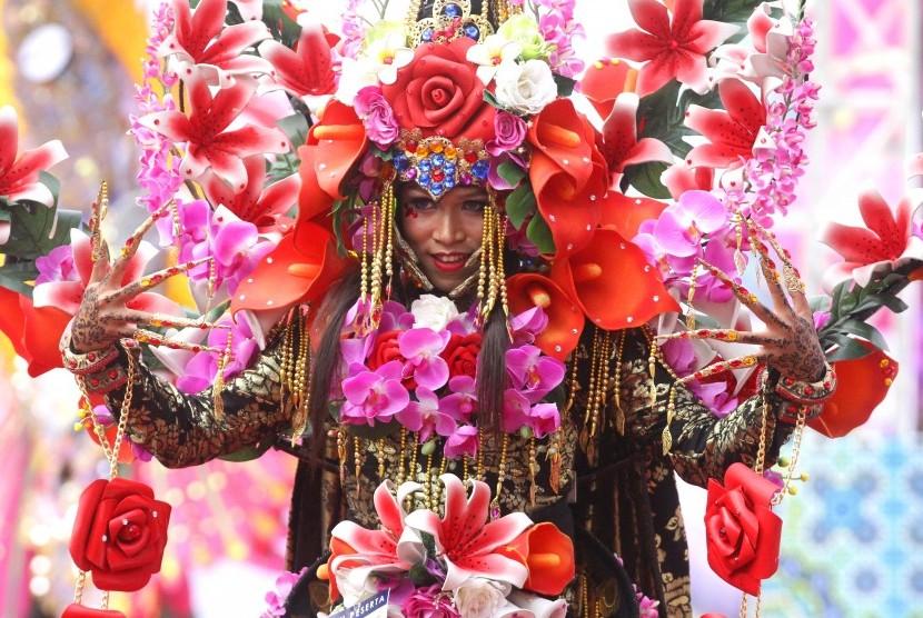 Model mempertontonkan keindahan busana bertema bunga anggrek dalam kegiatan Malang Fahion Flower Carnival dengan tema Eksotika Bunga Nusantara di Jalan Ijen, Malang, Jawa Timur, Minggu (10/9).
