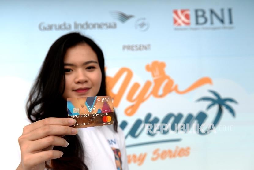 Model menunjukan kartu kredit BNI Style Titanium saat peluncuran ulang di Hanggar GMF AeroAsia Bandara Internasionao Soekarno-Hatta, Banten, Ahad (23/7).