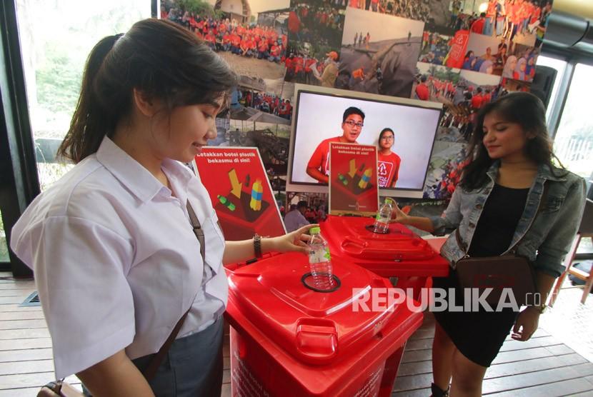 Model menunjukkan cara membuang sampah botol plastik saat peluncuran program Plastic Reborn yang diluncurkan Coca Cola di Jakarta, Selasa (27/2).
