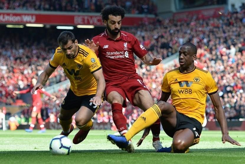 Mohamed Salah berebut bola dengan pemain Wolves dalam pertandingan di Stadion Anfield, Ahad (12/5)