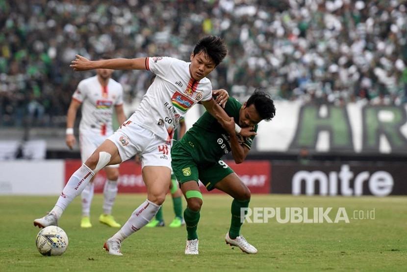Muhammad Hidayat (kanan) dan Feby Eka Putra (kiri) berebut bola  pada pertandingan Liga 1 Indonesia di Stadion Gelora Bung Tomo, Surabaya, Jawa Timur, Sabtu (24/8).