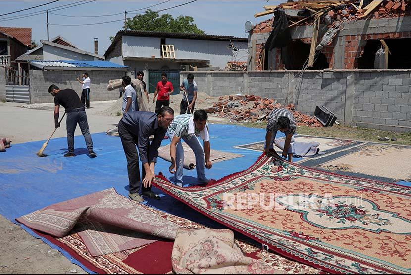 Muslim Belgrade Serbia menyiapkan karpet untuk Shalat Jumat di depan masjid yang telah dirobohkan oleh pemerintah setempat di Disktrik Zemun Polje, Belgrade, Serbia, Jumat (2/7). Pemerintah menganggap bangunan didirikan secara ilegal sehingga harus dirobohkan/