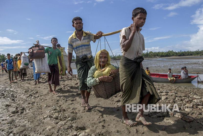 Muslim Rohingya, yang menyeberang dari Myanmar ke Bangladesh, membawa seorang wanita tua masuk dalam keranjang dan berjalan menuju sebuah kamp pengungsi di Shah Porir Dwip, Bangladesh (ilustrasi)
