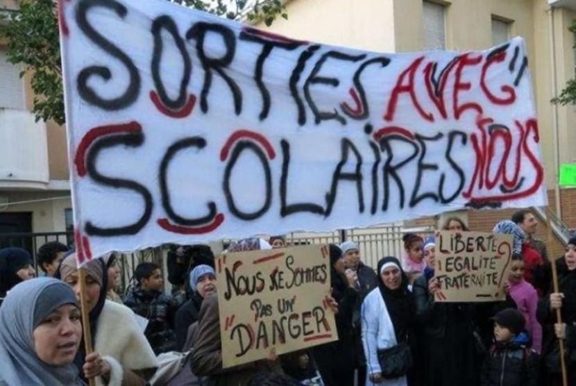 Muslimah di Prancis berdemontrasi menentang pelarangan pengenaan jilbab di lua ruang.