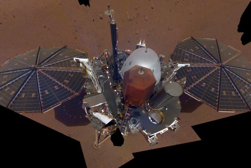 InSight berada di permukaan Mars. InSight menggunakan lengan robotik yang panjang untuk mengambil gambar-gambar planet tersebut