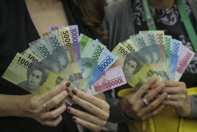 Nasabah menukarkan uang kertas rupiah pecahan lama ke pecahan baru tahun emisi 2016 di Kantor Perwakilan Bank Indonesia (BI) Kepulauan Riau, Batam, Senin (19/12).