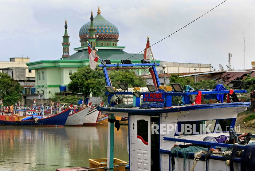 Nelayan berbaring diatas kapal yang ditambatkan saat libur melaut memperingati tsunami di Banda Aceh, Aceh, Selasa (26/12).