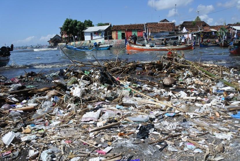 Nelayan melintasi muara sungai yang tercemar sampah plastik. (ilustrasi)