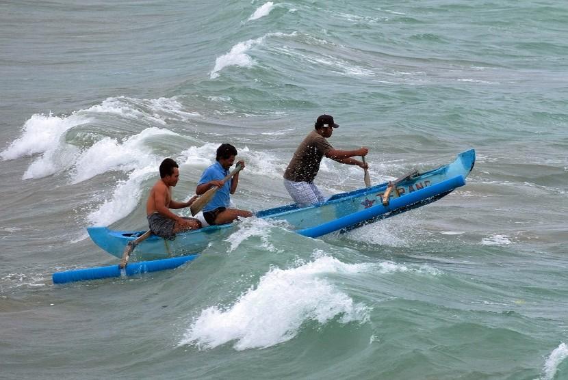 Nelayan menerobos ombak saat hendak menyelamatkan perahu yang diparkir di tengah laut Kedonganan, Badung, Bali, Sabtu (29/12/2018).