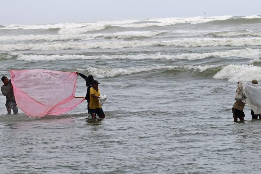 Nelayan menjaring anak ikan saat gelombang tinggi.