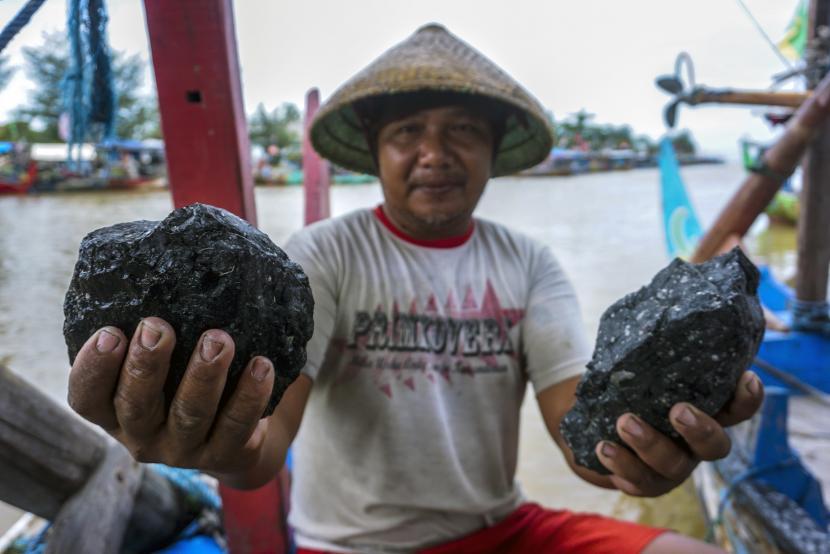 Nelayan menunjukkan bongkahan batu bara yang tersangkut jaring ikan usai melaut di Roban Timur, Subah, Kabupaten Batang, Jawa Tengah, Selasa (22/12/2020). Sejumlah nelayan setempat mengeluh jaring penangkap ikannya rusak dan merugi hingga 50 persen akibat tersangkut batu bara yang berasal dari kapal pengangkut batu bara di sekitaran perairan laut yang berdekatan dengan PLTU Batang.