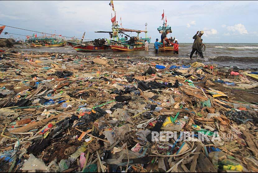 Nelayan menyandarkan perahunya di bibir pantai yang dipenuhi sampah plastik di Desa Dadap, Indramayu, Jawa Barat, Senin (26/11/2018). LSM World Wild Fund for Nature (WWF) Indonesia menilai masalah pencemaran sampah plastik di laut Indonesia sangat parah.