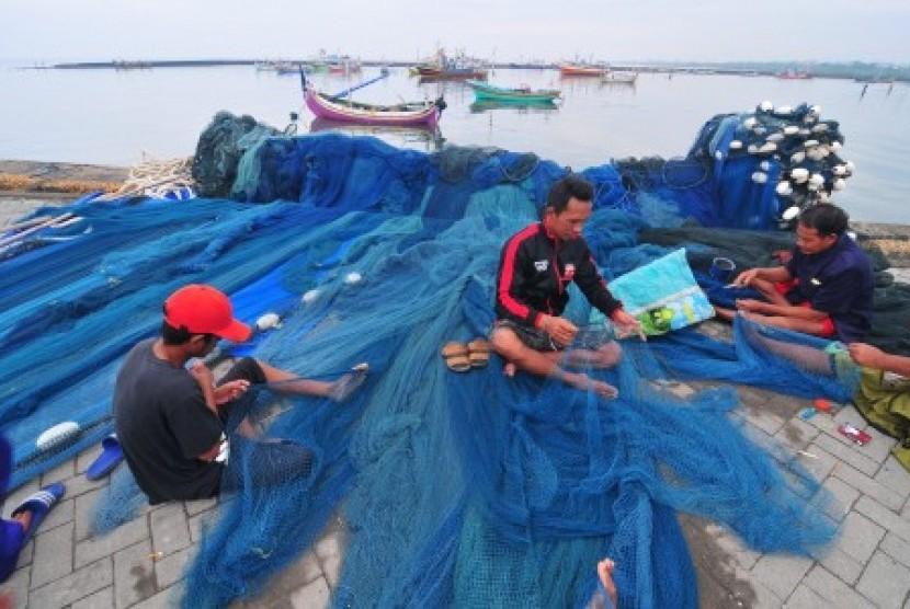 Nelayan yang tidak melaut memperbaiki jaring di Pelabuhan Branta Pesisir, Tlanakan, Pamekasan, Jawa Timur, Selasa (28/11). Sebagian nelayan di daerah itu tidak melaut menyusul peringatan BMKG terkait Badai Siklon Tropis yang meliputi sejumlah daerah di Indonesia termasuk Jawa Timur dengan potensi tinggi gelombang antara 2,5 meter hingga enam meter.