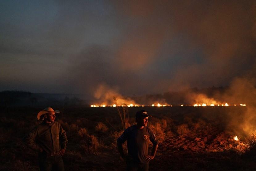 Neri dos Santos Silva (tengah) menyaksikan api yang mengancam peternakan tempatnya bekerja di kotamadya Nova Santa Helen, negara bagian Mato Grosso, Brasil, Jumat (23/8). Api itu bagian dari kebakaran yang terjadi di wilayah hutan Amazon.