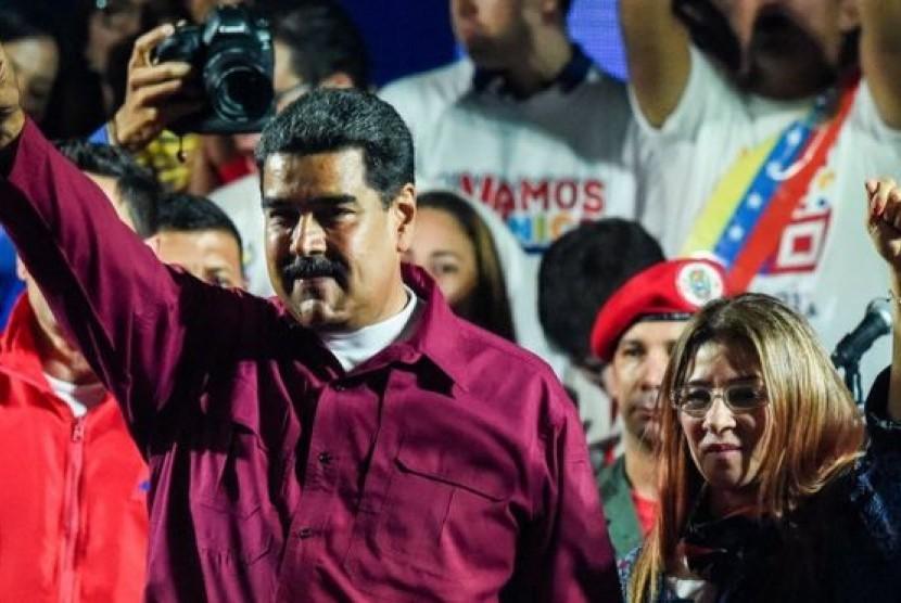 Nicolas Maduro merayakan kemenangannya di Pilpres bersama istrinya, Cilia Flores, Ahad (20/5).