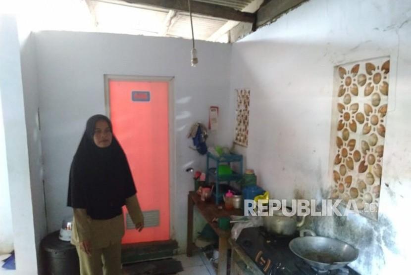 Nining (44) guru honorer di  SD Negeri Karya buana 3, Kecamatan Cigeulis, Kabupaten Pandeglang, terpaksa harus tinggal di toilet sekolah tempatnya mengajar karena kondisi ekonomi yang lemah, Senin (15/7).