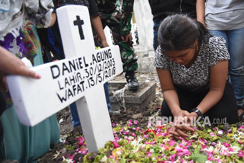 Novi (kanan) kakak dari Daniel Agung Putra Kusuma korban bom bunuh diri di Gereja Pantekosta Pusat Surabaya (GPPS) berada disamping pusara ketika pemakaman di Makam Putat Gede Surabaya, Jawa Timur, Selasa (15/5).
