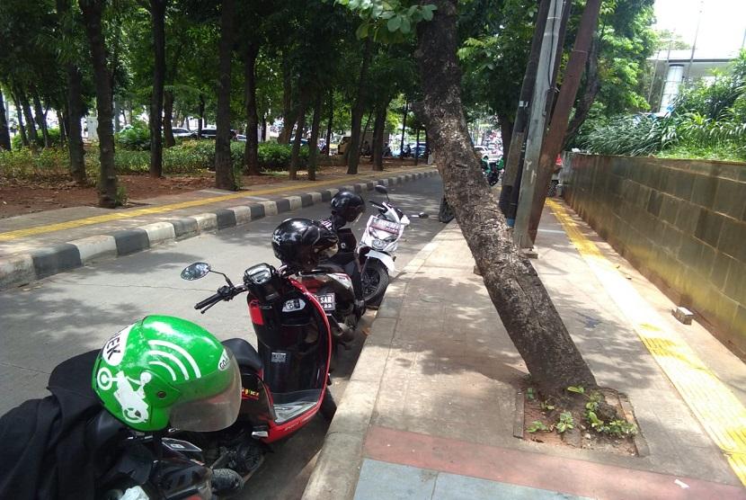 Ojek online memarkir kendaraan di tepi jalan di depan Pejaten Village