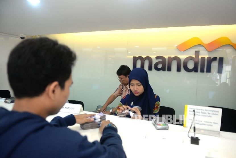 Nasabah menyetorkan uang tunai di salah satu cabang Bank mandiri, Jakarta, Jumat (6/5).  (Republika/Wihdan Hidayat)