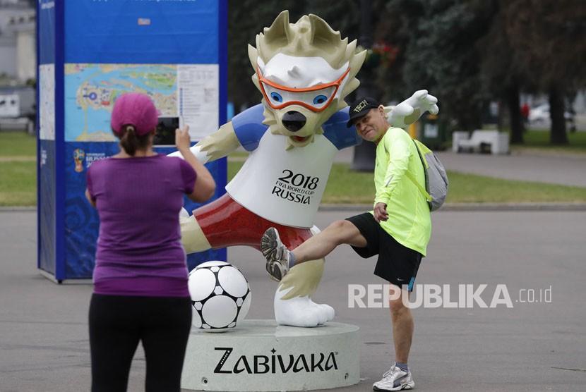 Orang-orang berfoto dengan maskot Piala Dunia 2018, serigala bernama Zabivaka,  di St. Petersburg, Rusia, Selasa (12/6). (