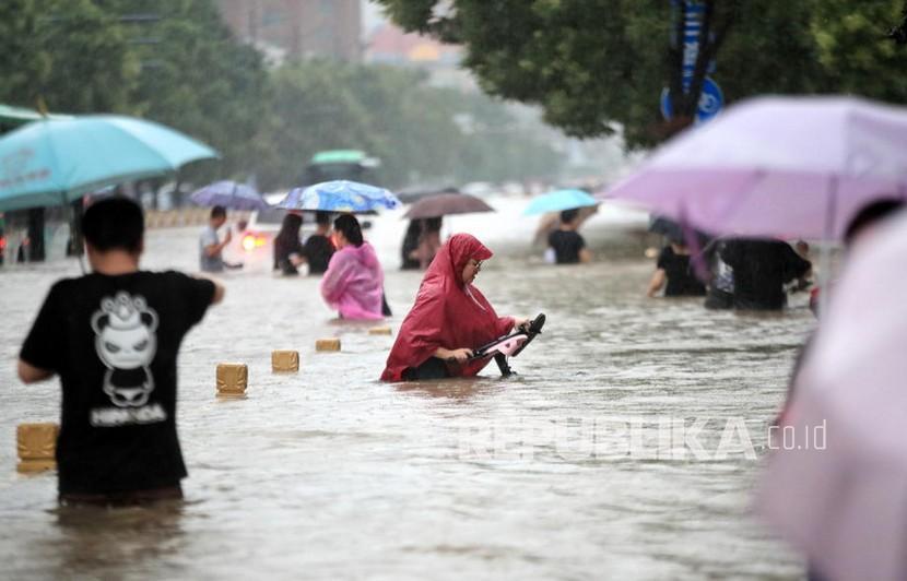 Orang-orang berjalan di jalan yang banjir setelah hujan deras yang melanda kota Zhengzhou di provinsi Henan, China tengah